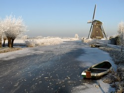 winter in holland at Kinderdijk, The Netherlands. Several windmills visible against a clear blue sky