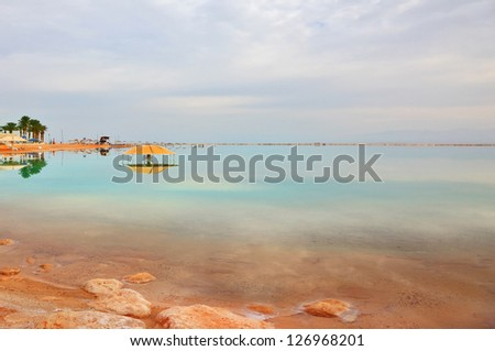 Winter in the Dead Sea. The comfortable high-rise hotel  is reflected in the sea smooth water