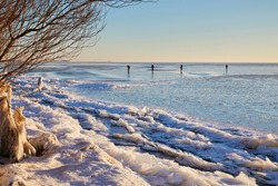Winter in the Netherlands. View on the frozen 'Markermeer' (lake) with ice skating men on dangerous ice. With in the distance the lighthouse of the former island Marken. Just after sunrise