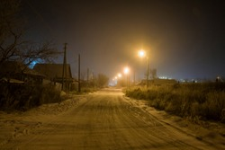 Winter in the village. Night shot of a road with lanterns