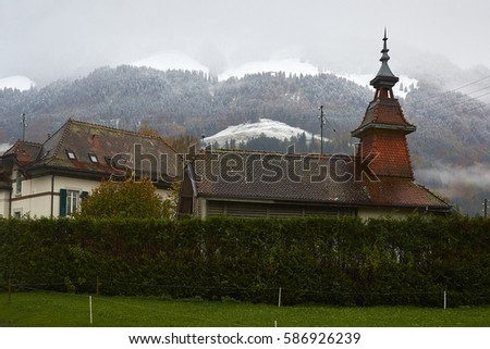 Winter is coming. A view of Dent de Broc and Dent du Chamois at the beginning of winter during snowing. The mountings are covering with snow while lowland is still dark green. Foto stock ©