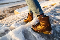 Winter is coming. Female boots on rough slipper ice surface. A woman in brown leather shoes descends the slippery ice ladder.