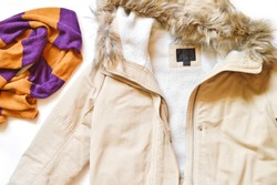 Winter jacket with faux fur and an orange and purple wool scarf. Flat lay women's outfit. Top view photo
