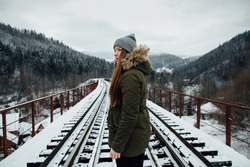 Winter journey. Girl in winter clothes on railway bridge in winter day.