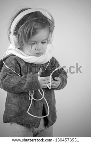 winter kid fashion. little girl child smiling. having fun. small happy girl. childhood and happiness. kid listen music with headset and mp3 on phone. Young expertise. Stylish and confident.