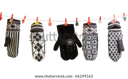 Winter knitted gloves hang on the Christmas lights in the clothes pins