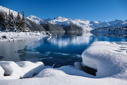 Winter lake with reflections of mountains in calm water. Garibaldi Lake in Whistler. British Columbia. Canada
