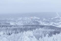 winter landscape - a distant metallurgical plant in a valley in the middle of snow-covered forests in a frosty haze