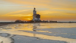 Winter landscape at the Lighthouse Paard van Marken Netherlands. On a cold day, temperature -7 degree during sunset. The IJsselmeer is frozen and by strong wind the shore was covered with ice