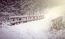 Winter landscape. Bridge covered in snow in forest.