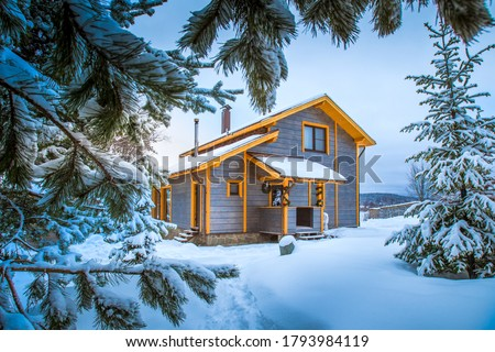 Photo of  Winter landscape. Cottage on the background of snow-covered fir branches. Wooden house in the countryside. Christmas and New year in cottages. Rent a country house for a large company.