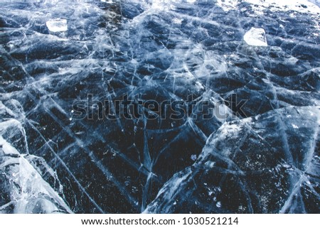 Winter landscape, cracked ground of frozen lake Baikal,Irkutsk, Siberia, Russia. Sunny winter day weather, ice cracks, clear water, slippy and cold frozen ground. Beautiful wallpaper with nature scene