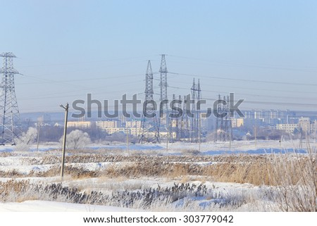 winter landscape dense fog over fields and high-voltage power line on the horizon at sunrise