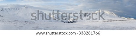 Winter landscape. Dramatic overcast sky.Severe mountains peaks covered by snow. Russia, Siberia, Altai mountains, Chuya ridge.
