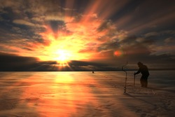 winter landscape fisherman fishing on the estuary Eek river at sunset