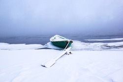 Winter landscape foggy morning on the river. Beautiful winter dawn on the river. Boats in the snow on the river in winter. An isolated boat covered in snow stands on the bank of a Foggy river in winte