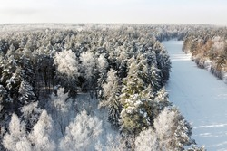 Winter landscape - frozen river and trees covered hoarfrost, aerial view. Winter forest with snowy trees in sunny frosty day, top view