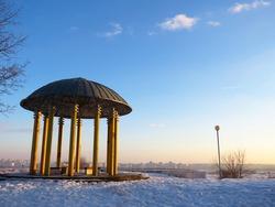 Winter landscape: gazebo against the background of the evening blue sky