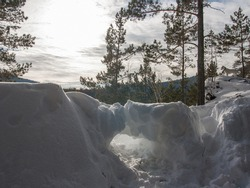 Winter landscape in a mountainous area. A bright spot of the sun in a blue sky with clouds. Large drifts of snow. A ray of sunlight breaks through a crack in the snowdrift.