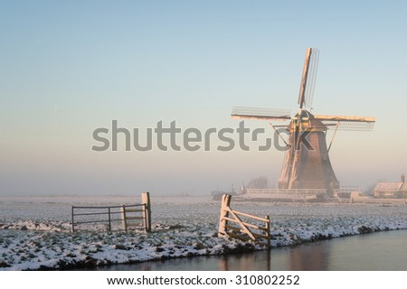 Winter landscape in Holland (the Netherlands) in a rural area with a windmill in a meadow, a fence, a canal, snow and fog at sunrise.