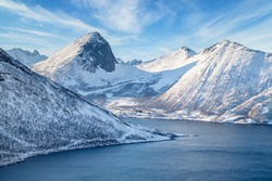 Winter landscape in Lofoten islands, Norway. Coastline of the fjord and snow-covered mountains.