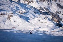 Winter landscape in the Alps. chalet house in Mayrhofen sports region in the Zillertal. Ski slopes in the background of mountains. Skiers descend a difficult black slope
