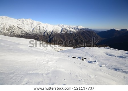 Winter landscape in the italian Alps with abandoned old alpine pasture huts, rocky boulders and smooth slopes covered by back country ski tracks.