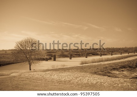 Winter landscape in the Netherlands with snow and wooden bollards in the ice. This image is processed in antique light; that creates a pleasant atmosphere effect.