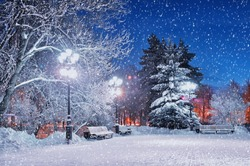 Winter landscape in the park -  snowy benches under falling snow and shining street  lights.Wonderland in night city
