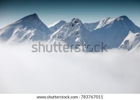 Winter landscape in the Western Tatras. Mountains in the winter. Mountains above the clouds. View of the Rohace peaks. Slovakia. #783767011