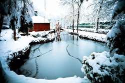 winter landscape of a frozen pond, cottage and water mill powdered with snow