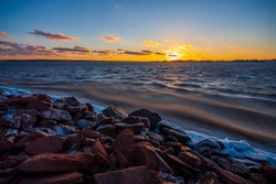 Winter landscape of a low sunset over choppy sea waters and a snowy rocky beach of Charlottetown, Prince Edward Island, Canada