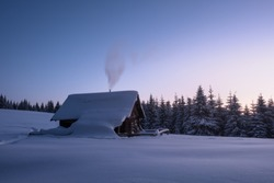 Winter landscape of a mountain forest with a cabin at sunset. Trail stamped in the snow towards the cabin. Fir-trees and a cabin covered with snow. Winter traveling. Smoke comes from the chemney.
