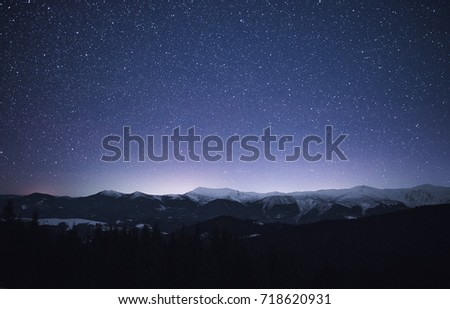 Winter landscape of a mountain range at night. Stars over the mountain range. Snow covers slopes of a mountains. #718620931