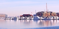 Winter landscape of Baltimore Inner Harbor. Yachts anchored at pier in winter.