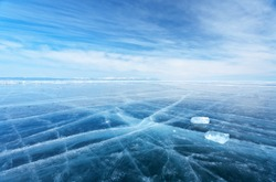 Winter landscape of frozen Baikal Lake. The endless fields of smooth blue ice and two transparent icicles on slippery ice surface. Cold natural background