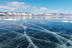 Winter landscape of frozen lake Baikal on a sunny February day. Beautiful blue smooth ice with cracks in the Small Sea Strait. Ice travel in winter holidays. Natural background (focus on ice)