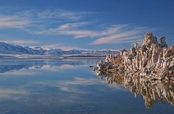 Winter landscape of Mono Lake with tufa formations, mirrored reflections in calm water, and Eastern Sierra Nevada Mountains, California, USA