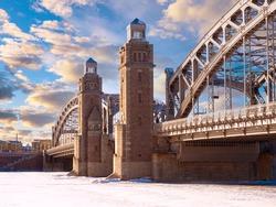 Winter landscape of Saint Petersburg. Russia bridge. Bolsheokhitinsky bridge view from embankment. Russia town on a sunny winter day. Bridge of Peter Great in Saint Petersburg. Russia snow.