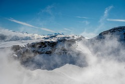 Winter landscape of snowcapped mountains with blue sky and clouds on sunny day. Famous Diablerets Glacier in Switzerland.