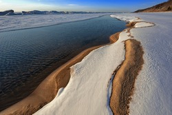 Winter landscape of the frozen shoreline of Lake Michigan near sunset, Saugatuck Dunes State Park, Michigan, USA