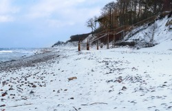 winter landscape of the sea coast, descent to the sea and snow on the beach