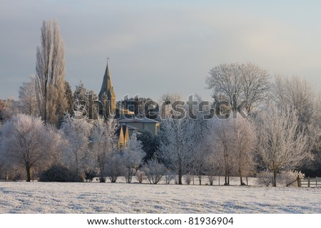 Winter landscape of village church spire and frozen trees, England