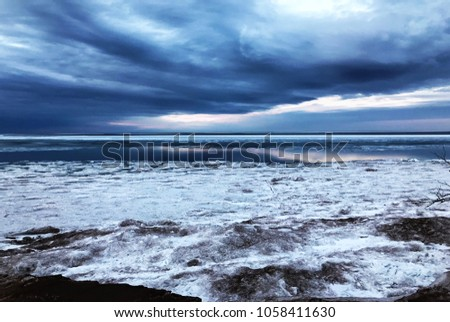 Winter landscape on Lake Superior in Marquette, MI. Sunset. Ice, snow and open water. Isolated. Interesting clouds. Upper Peninsula Michigan #1058411630