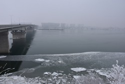Winter landscape on the big river. Across the river is a strong concrete bridge. Along the riverbank is ice and icebergs.