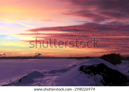 Stock Photo winter landscape red sunset on the ice of the river and and pipe plant on the horizon