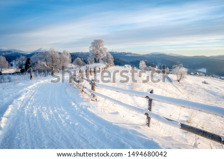 winter landscape. rural road covered with snow. mountains on horizon #1494680042