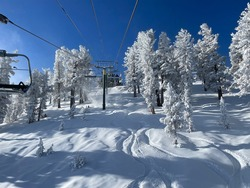 Winter landscape scene at a ski resort, with snow covered trees and slopes, on a bluebird day