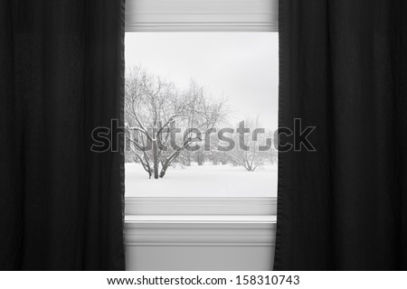Winter landscape seen through the window with black curtains.
