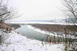 Winter landscape, the bed of a wide river and the bank in the snow, view from the top